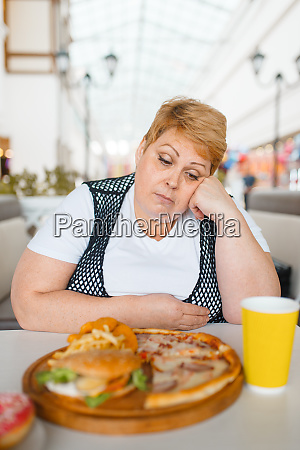 fatty woman eating pizza in fastfood
