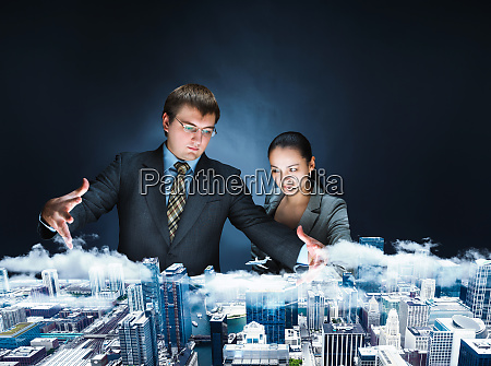 powerful businesspersons looking on model of