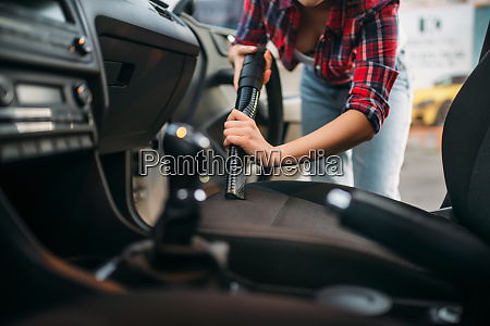 woman cleans car interior with vacuum