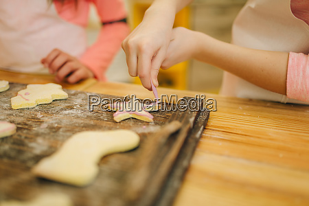 little girls cooks cover cookies with