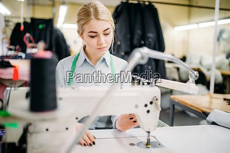 dressmaker sews fabrics on a sewing