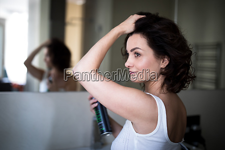 beautiful young woman styling her hair