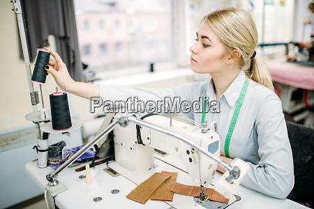 female dressmaker sews on serger machine