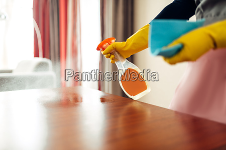 housemaid hands cleans table with cleaning
