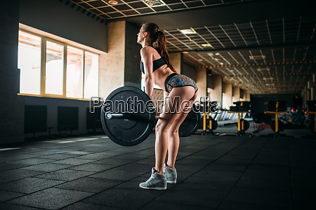 female athlete training with barbell in