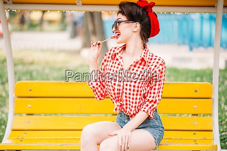 sexy pinup girl licks sweet lollipop