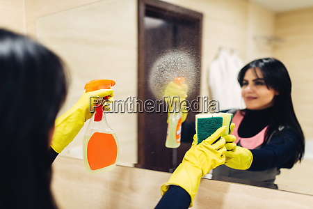housemaid cleans the mirror with a