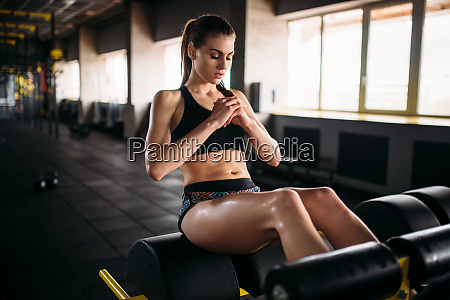 slim female athlete trains press in