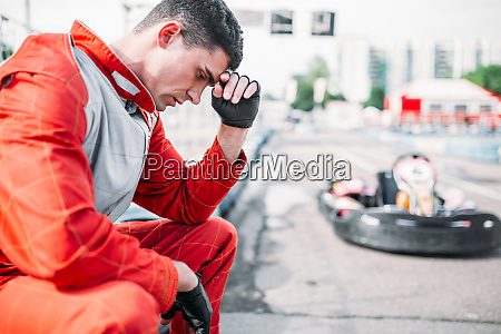 karting racer sits on a tire