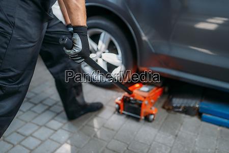 auto mechanic jacks the car in