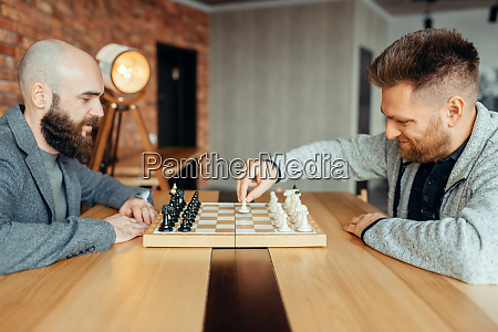 male chess players begin playing the