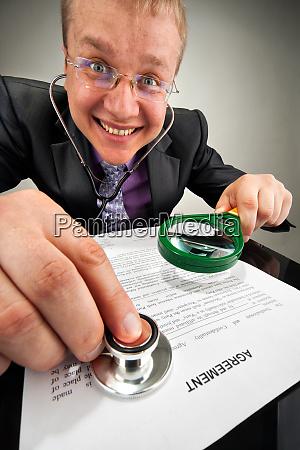 bizarre businessman examining the agreement