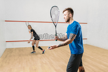 couple with squash rackets indoor training