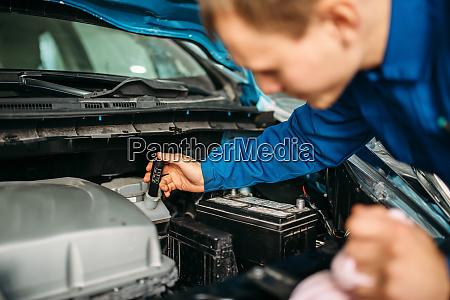male technician checks brake fluid level