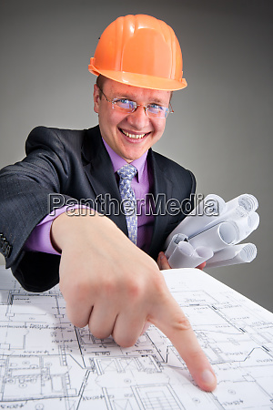 happy contractor pointing to plans