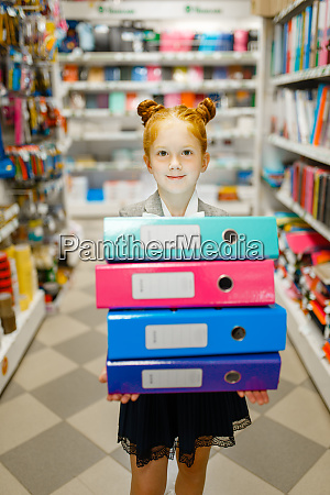 school girl holds folders in stationery