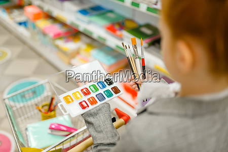 schoolgirl choosing watercolor paints stationery