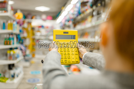 schoolgirl holds calculator stationery store