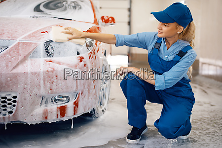 female washer wipes the automobile headlights