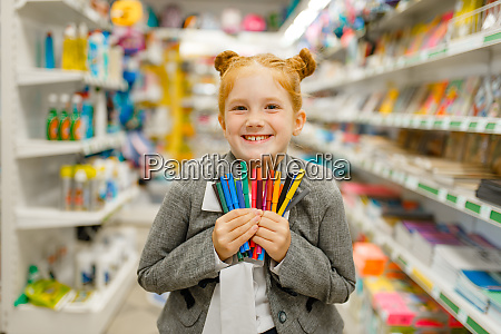 school girl holds markers stationery store