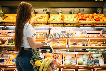 female customer against fruit section in