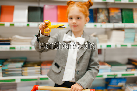 schoolgirl choosing scissors in stationery store