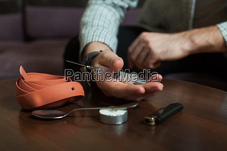 addict preparing a dose of heroin