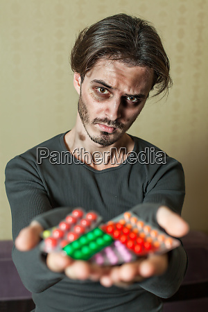 drugs addict is holding tablets in