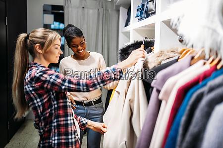 two girlfriends choosing clothes shopping