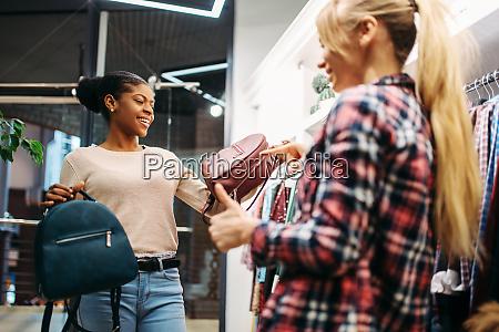 two females choosing bags in shop