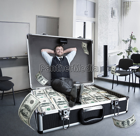 happy businessman sits in the case