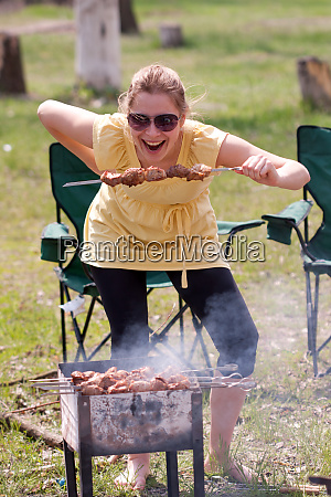 woman grilling shish kebab