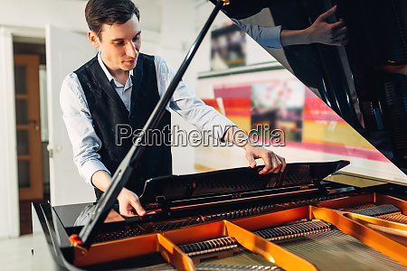 male pianist opens the lid of