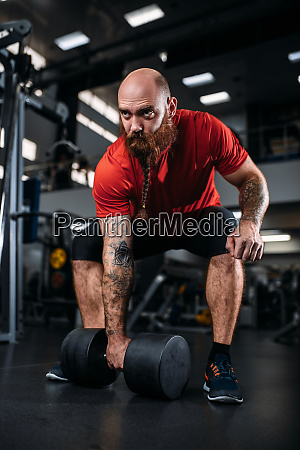 male lifter doing exercise with dumbbells