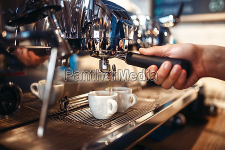 barista hand pours beverage from coffee