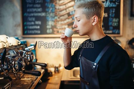 young barista tastes fresh prepared coffee