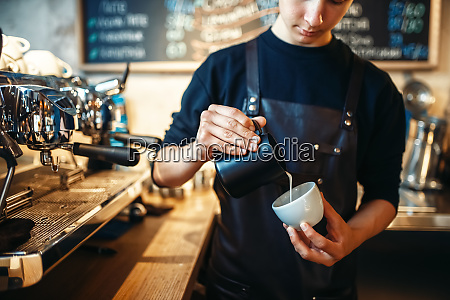 barista pours cream into the cup