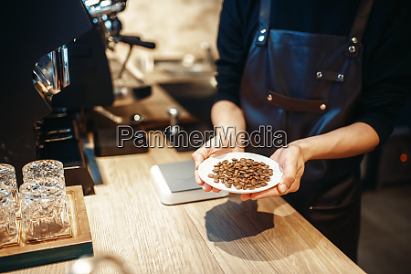 barista holding plate with fresh coffee