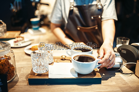 barista hand with cup of fresh
