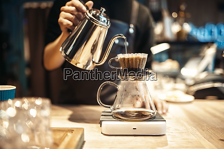 male barista pours boiling water into