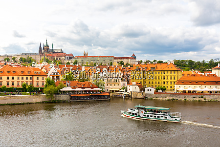 prague cityscape with pleasure boat on