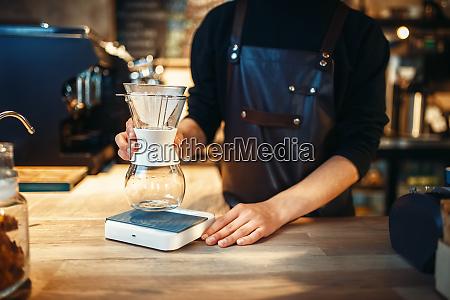 male barista puts a glass of