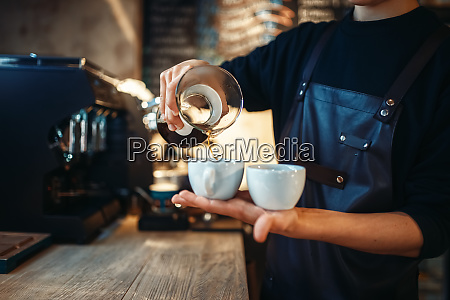 young male barista holds two cups