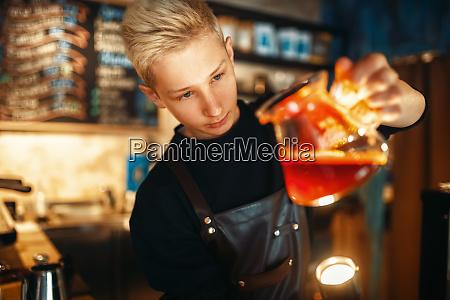 male barista checks the sediment in