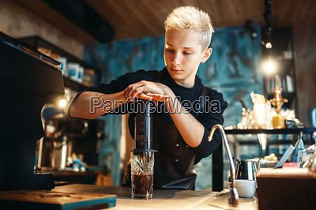 young male barista makes fresh espresso