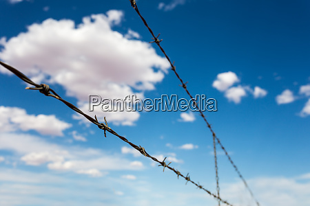 barbed wire againdt blue cloudy sky