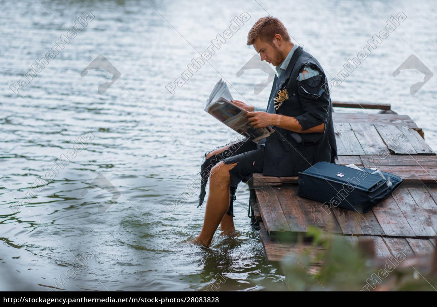 businessman, reading, newspaper, on, desert, island - 28083828