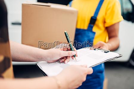 male, worker, in, uniform, gives, parcel - 28083413