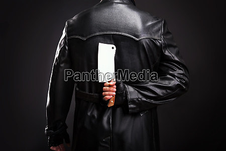 serial murderer holding meat cleaver behind