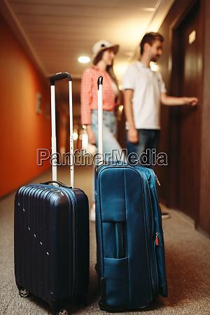suitcases in hotel hallway couple open